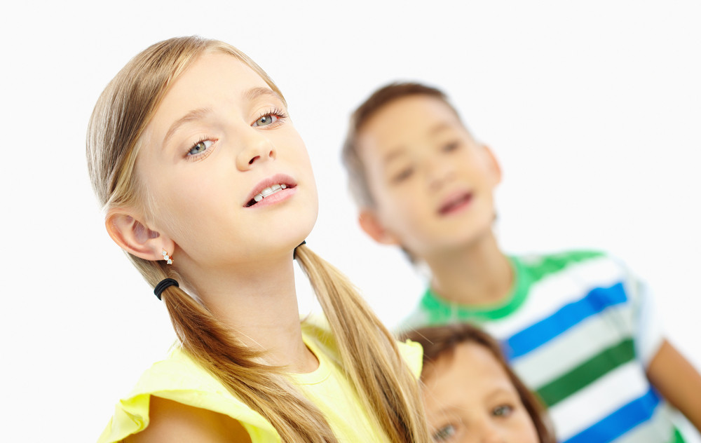 Portrait Of Attentive Girl And Her Classmates Listening To The Teacher At Lesson