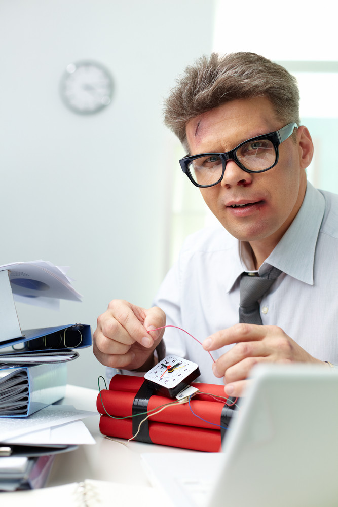 Serious Man Preparing Dynamite With Big Heaps Of Papers Near By