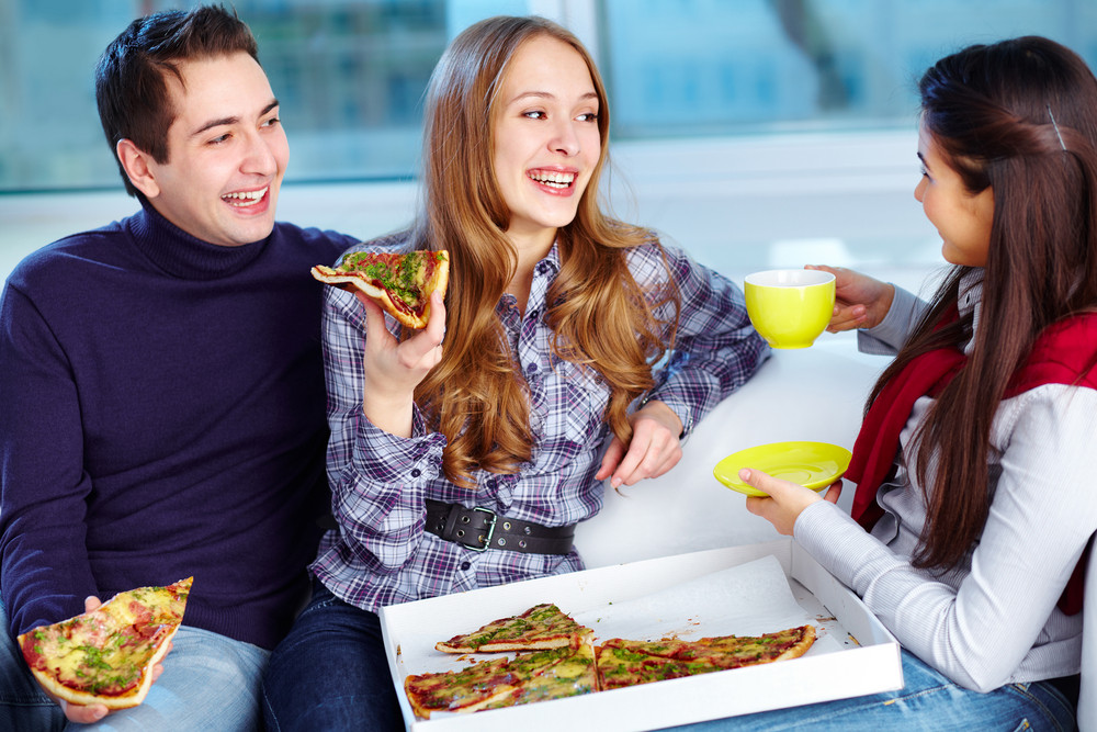 Image Of Happy Teenage Friends Eating Pizza Together