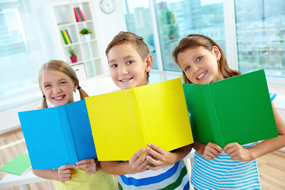 Portrait Of Happy Classmates With Multi-colored Open Books Smiling At Camera In Classroom