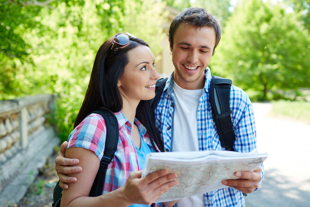 Couple Of Travelers With Map Discussing Where To Go