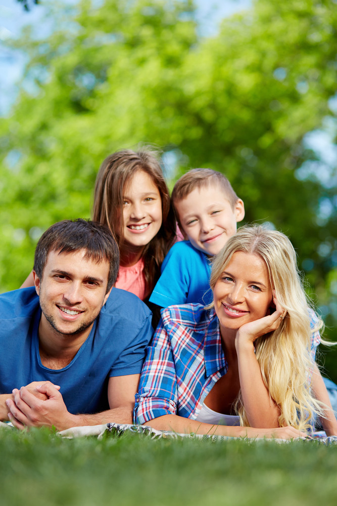 Photo Of Happy Family Of Four Relaxing On Grass During Summer Rest
