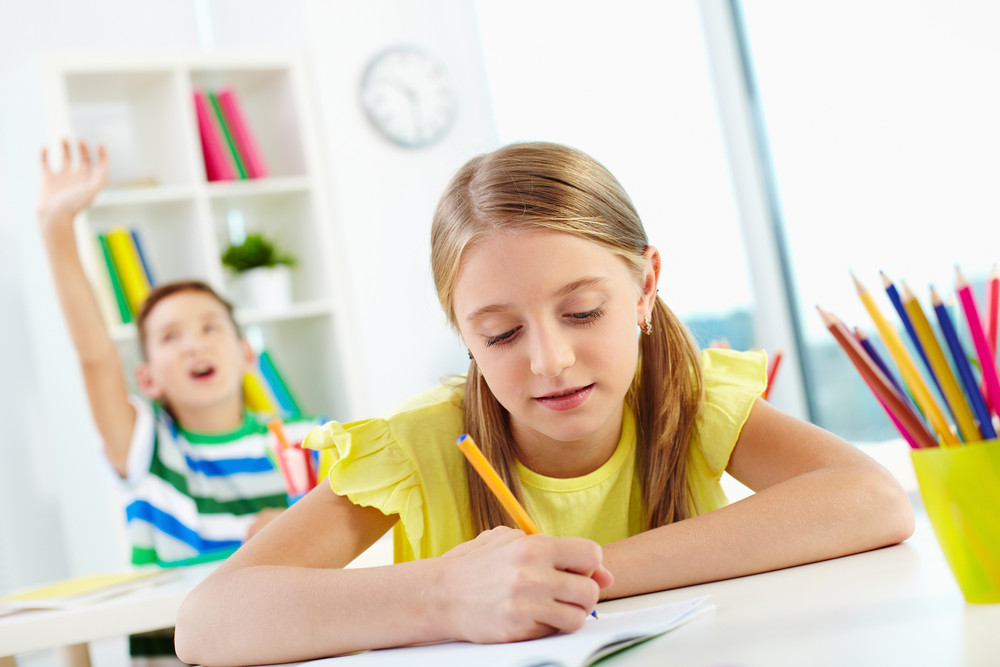 Portrait Of Lovely Girl Drawing At Workplace With Schoolmate Raising Hand On Background