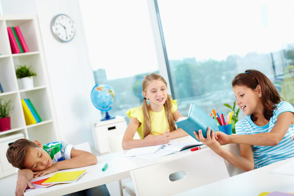 Cute Schoolgirl Showing Her Classmate Her Notes