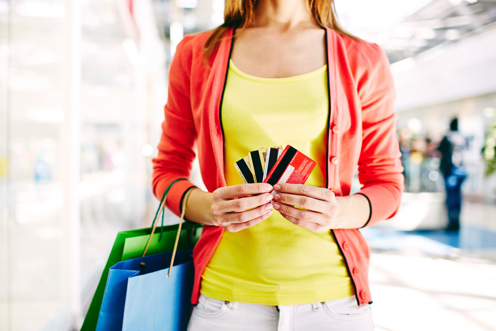 Female Customer With Plastic Cards And Shopping Bags In The Mall