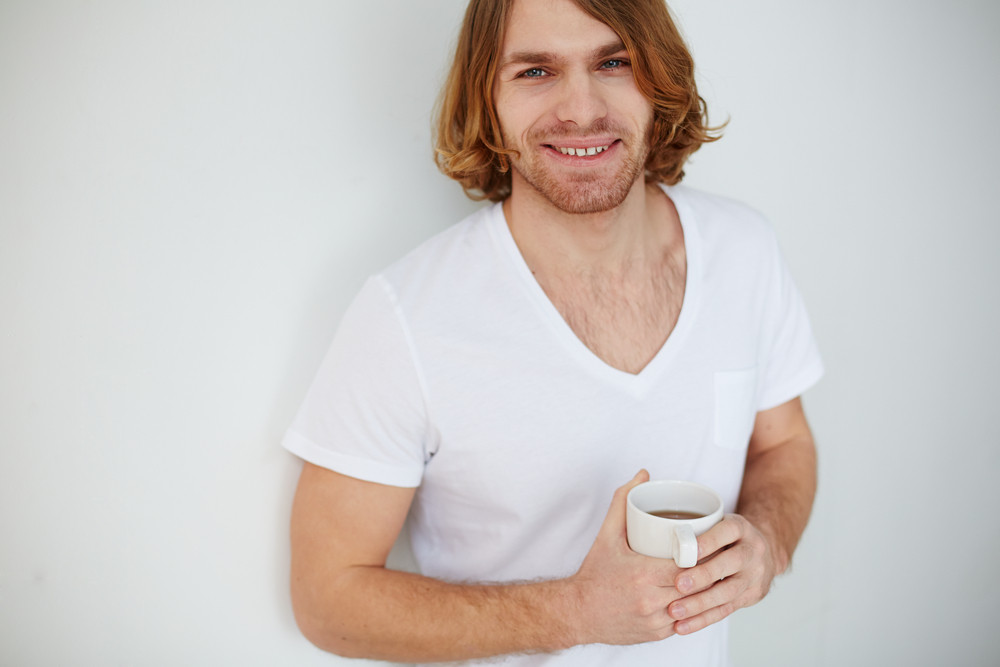 Photo Of Young Man With Cup Of Tea Looking At Camera And Smiling
