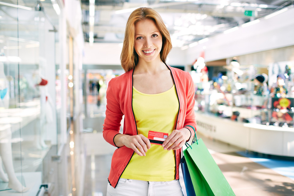 Female Customer With Plastic Card And Shopping Bags Looking At Camera In The Mall