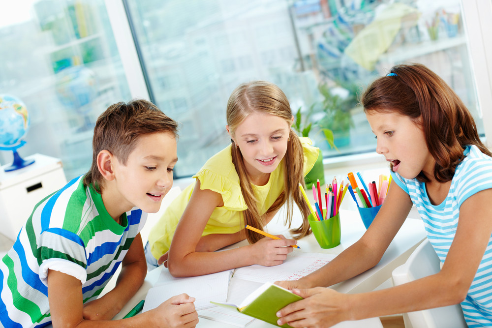Group Of Curious Classmates Looking At Note In Notebook In Girl Hands At Workplace