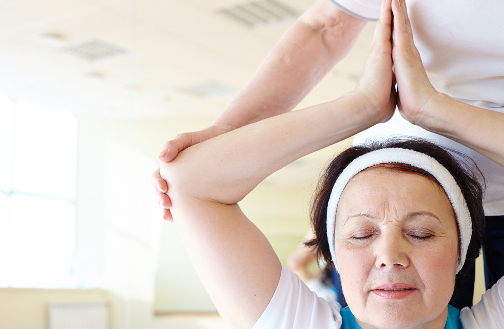 Portrait Of Aged Female Doing Yoga Exercise In Sport Gym