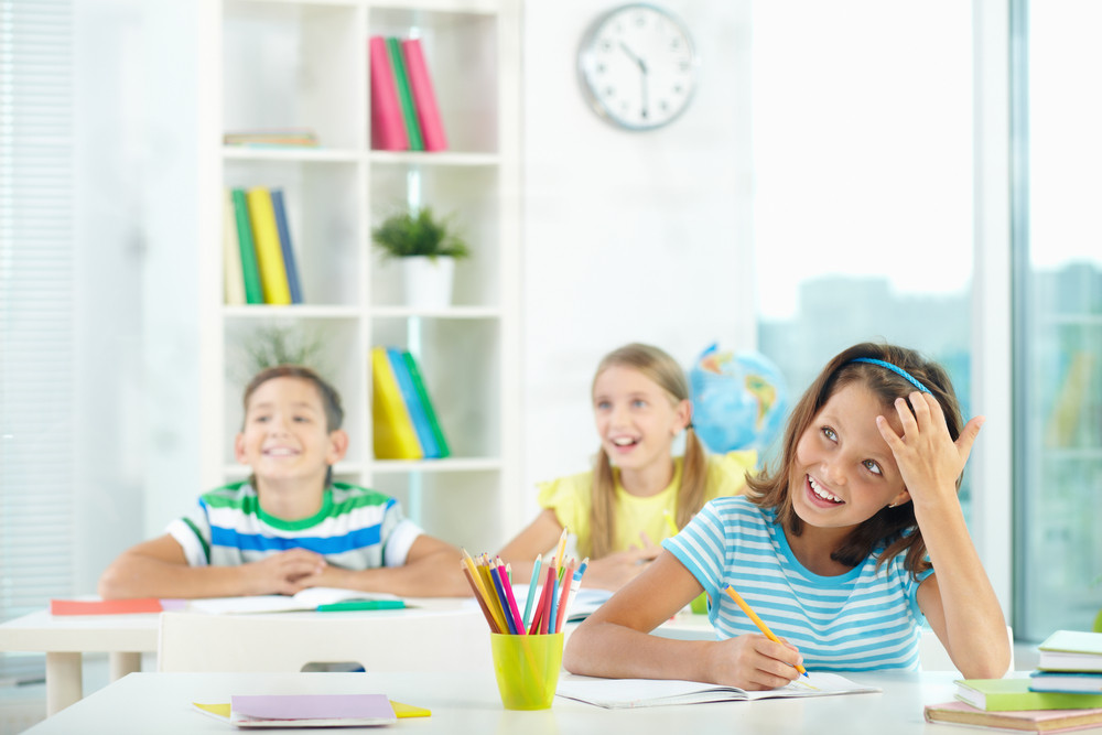 Portrait Of Cute Girl And Her Two Schoolmates On Background Looking At Something Attentively At Lesson