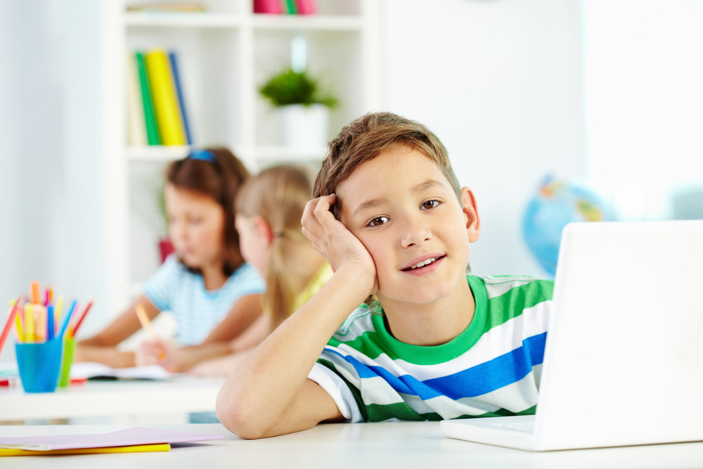 Portrait Of Smart Lad At Workplace Looking At Camera With Two Classmates On Background