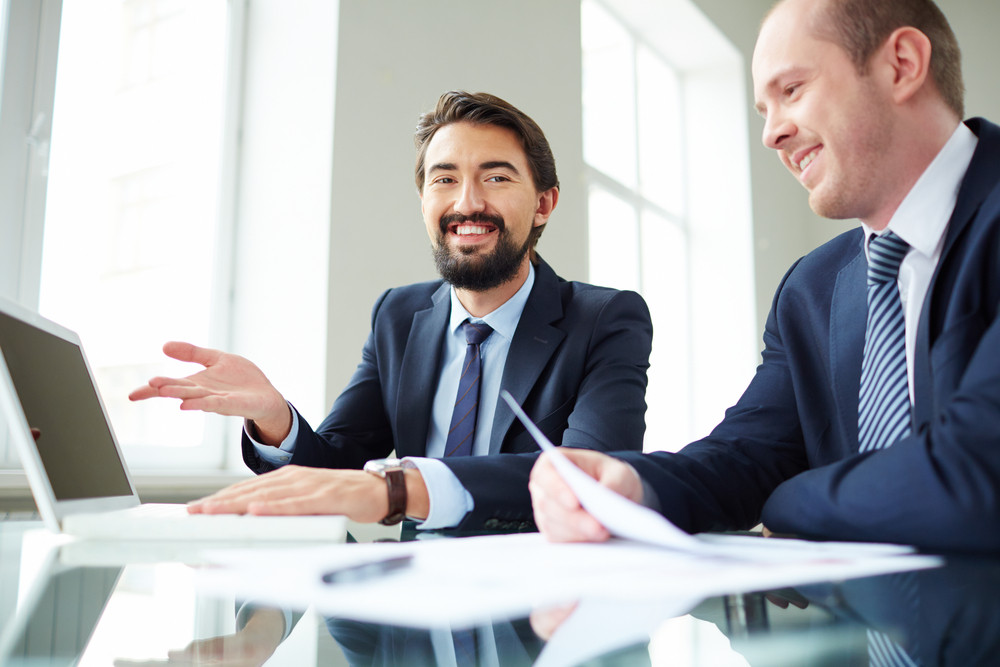 Image Of Smiling Businessman Pointing At Laptop Screen While Explaining Ideas To His Colleague At Meeting And Looking At Camera