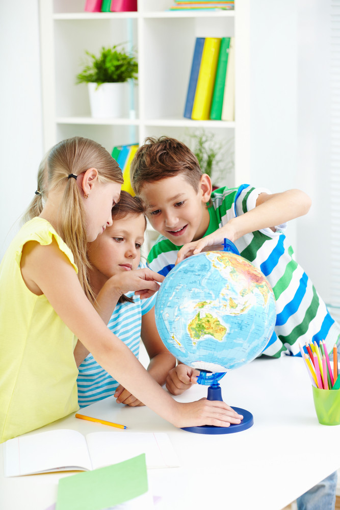 Portrait Of Curious Classmates At Workplace Studying Globe In Classroom