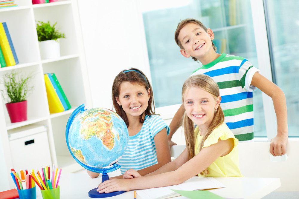 Portrait Of Happy Classmates At Workplace Looking At Camera In Classroom
