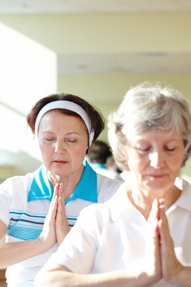 Portrait Of Two Aged Females Doing Yoga Exercise For Balance In Sport Gym