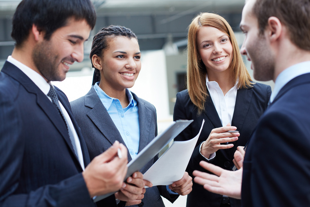 Group Of Business Partners Looking At Their Colleague While Interacting At Meeting