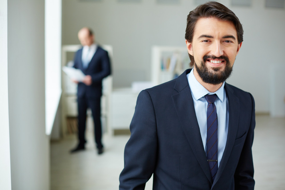 Image Of Young Businessman In Suit Looking At Camera On Background Of His Colleague