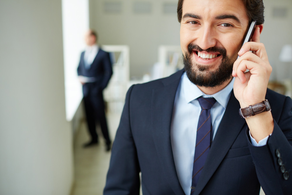 Image Of Young Businessman Speaking On The Phone And Looking At Camera On Background Of His Colleague