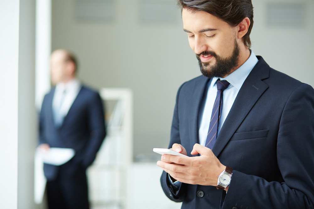 Image Of Young Businessman Using Smartphone On Background Of His Colleague
