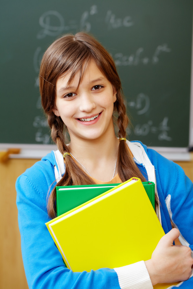 Portrait Of Pretty Girl By The Blackboard Looking At Camera