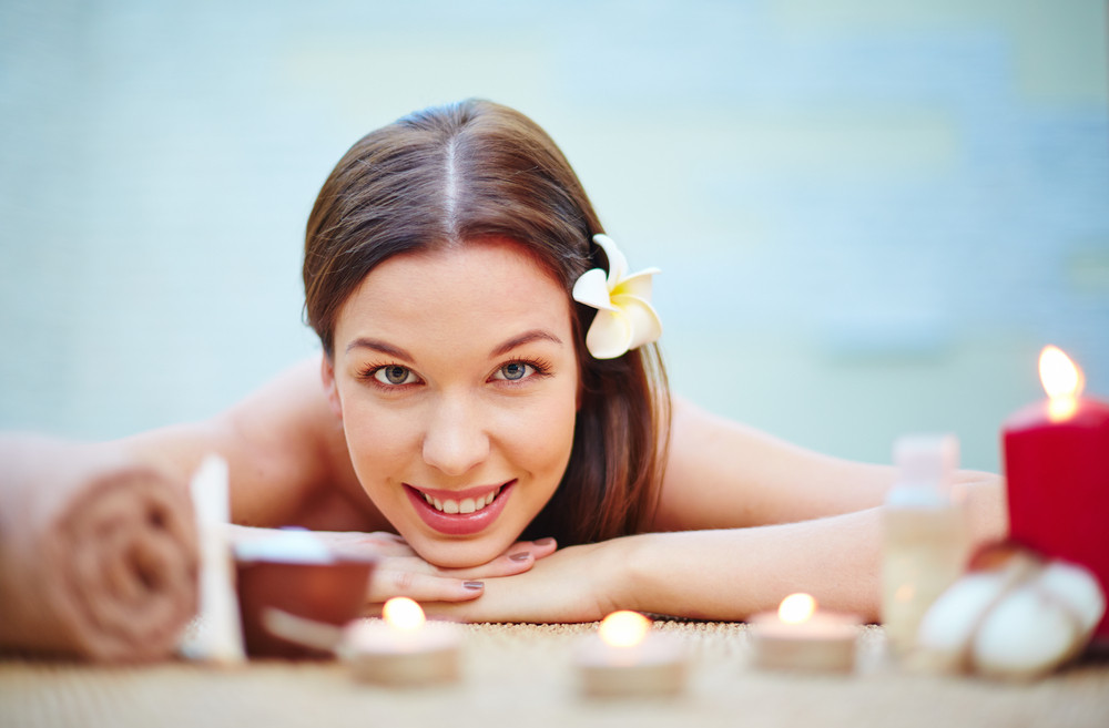 Happy Girl With Frangipani Flower In Hair Relaxing In Spa Salon