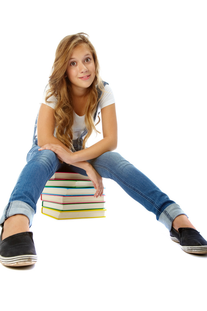 Pretty Teenager On Heap Of Books Looking At Camera In Isolation