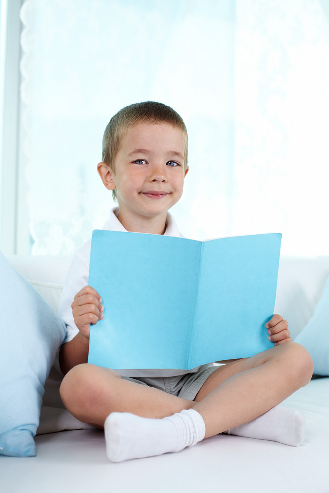 Little Boy Sitting On Sofa With Book