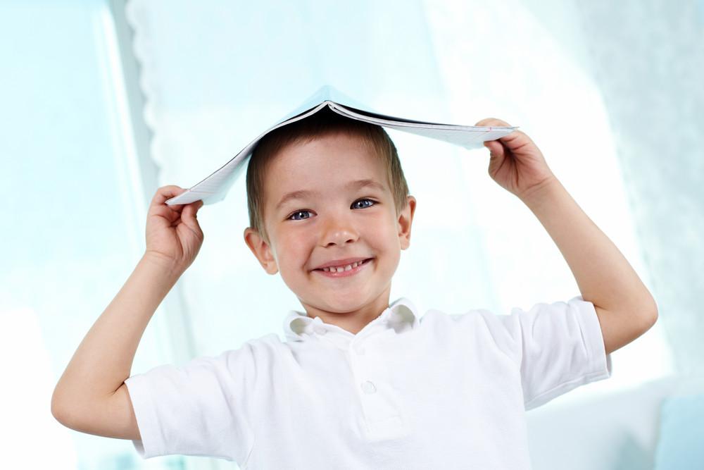 Happy Little Boy Keeping Copybook On His Head