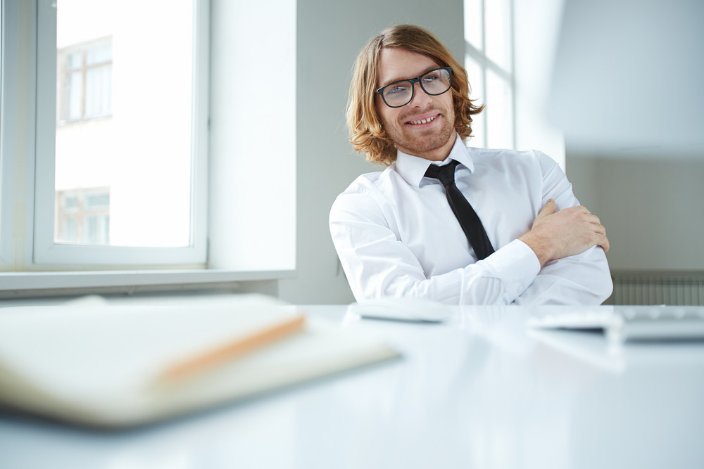 Portrait Of An Office Worker Sitting At Workplace And Looking At Camera With Smile