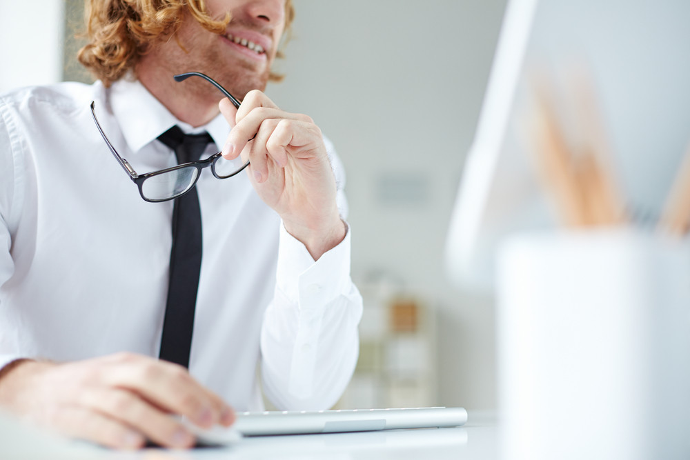 Office Worker Sitting At Computer And Looking At The Screen With Interest