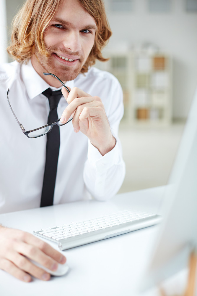 Portrait Of Handsome Man At Computer Looking At Camera