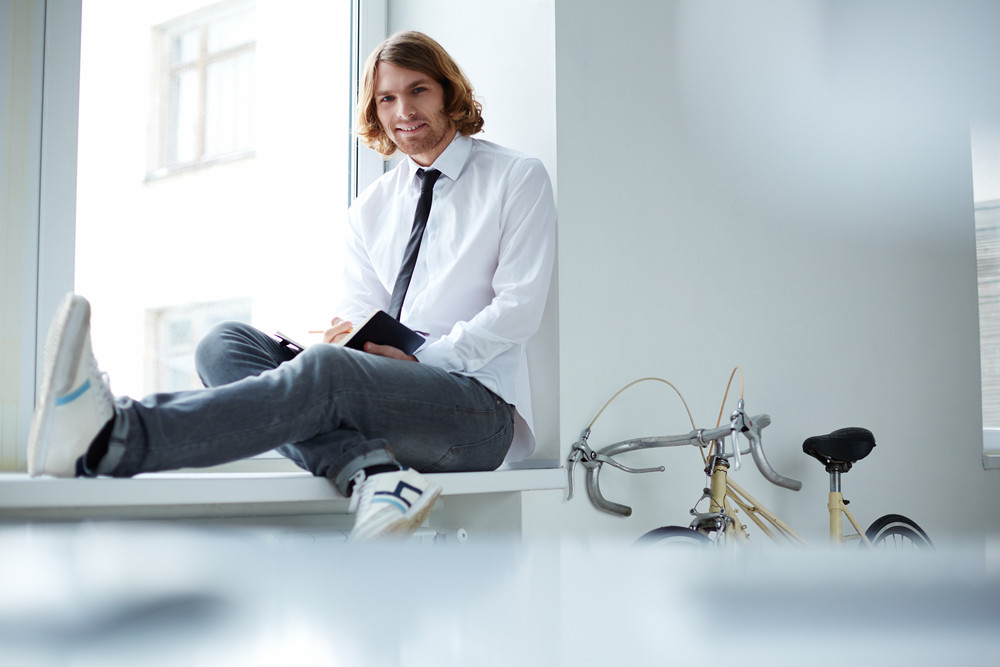 Young Businessman Sitting On Window-sill In Snickers