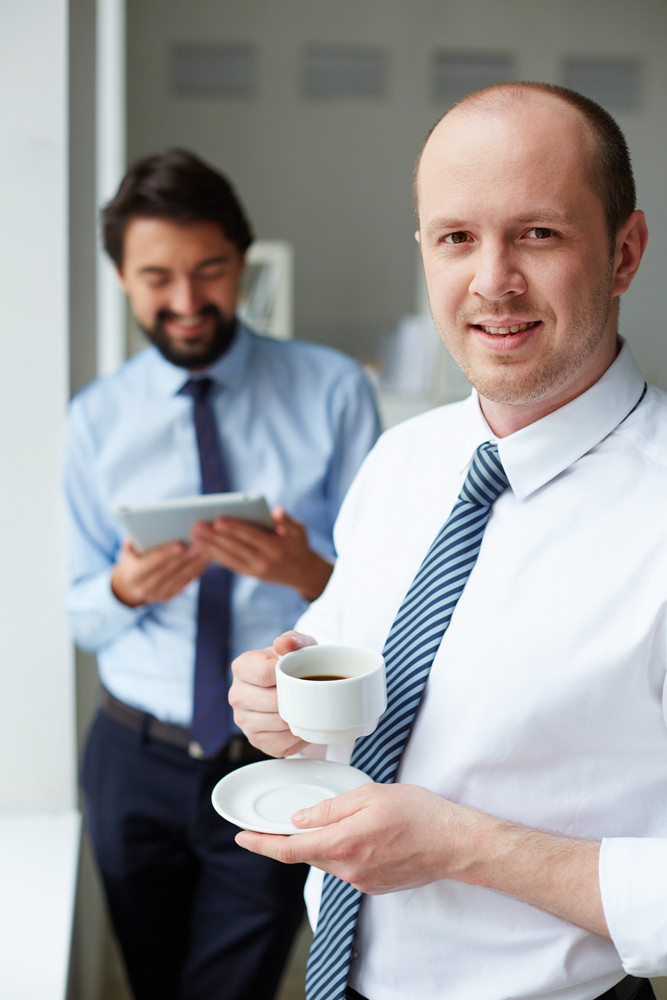 Image Of Young Businessmen With Cup Of Coffee Looking At Camera In Office
