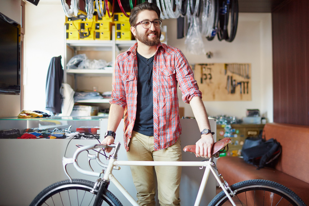 Portrait Of A Handsome Man With Bicycle In Sports Shop