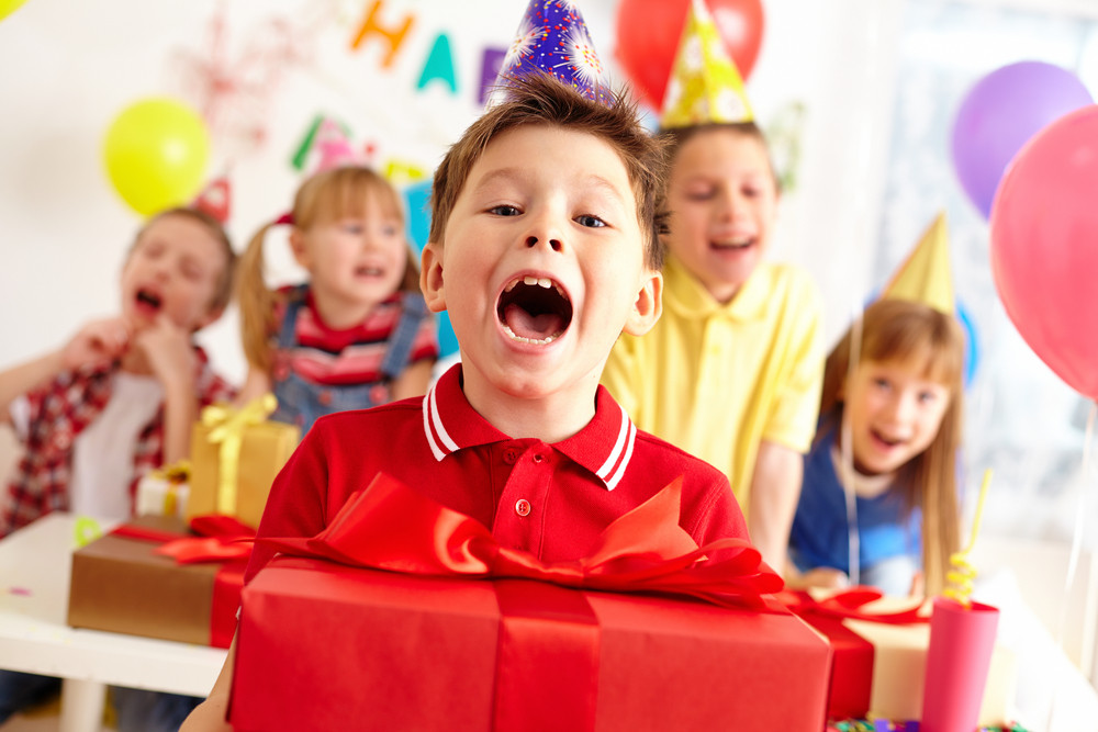 Joyful Boy With Big Red Giftbox Looking At Camera With His Friends On Background