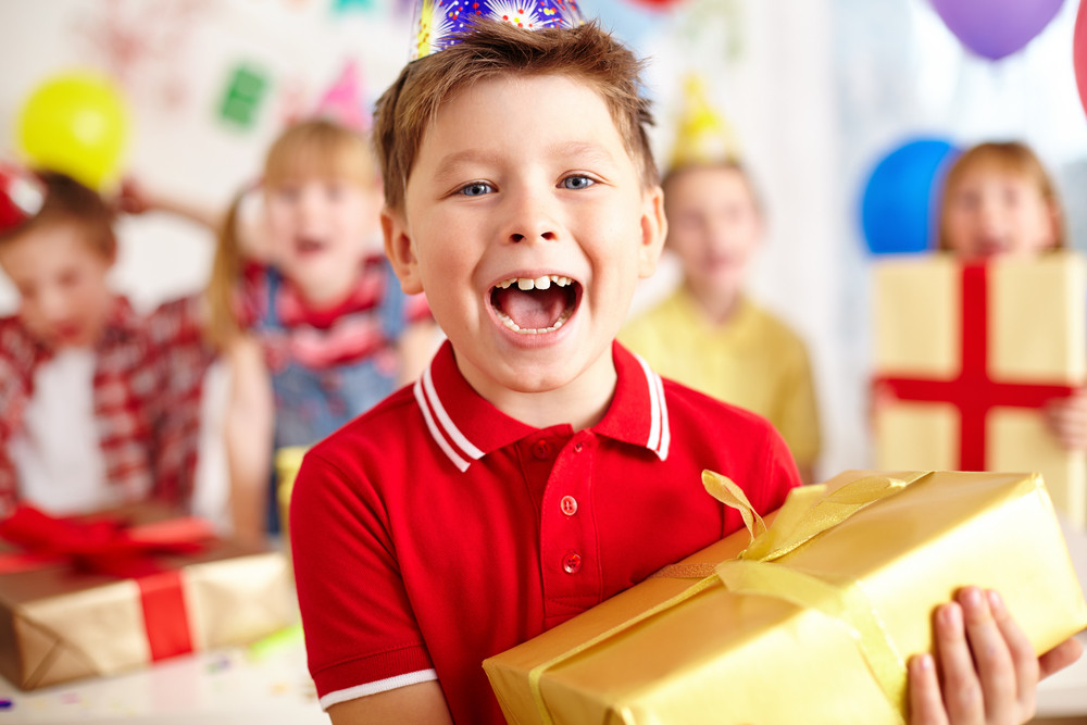 Excited Lad With Big Red Giftbox Looking At Camera With His Friends On Background