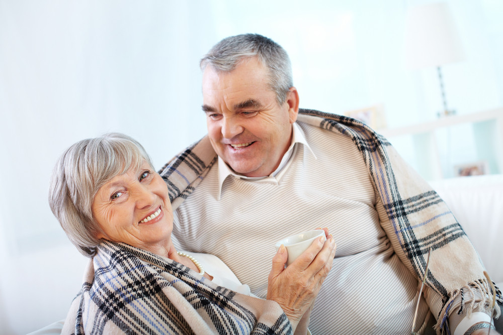 Portrait Of A Happy Senior Couple Wrapped In Plaid Sitting At Home
