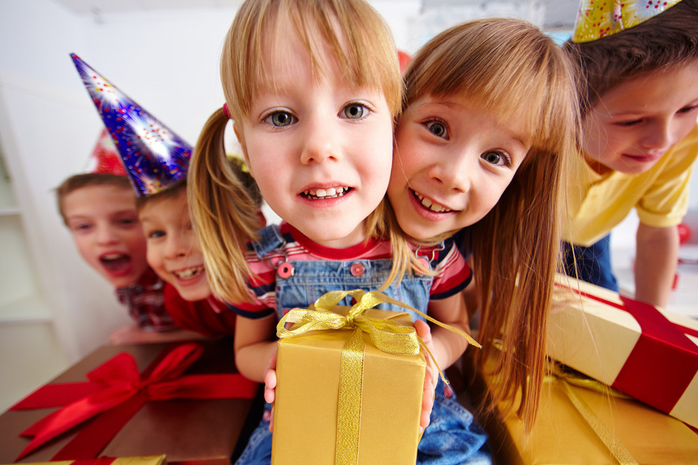 Joyful Girls With Gifts Looking At Camera With Three Cute Boys On Background