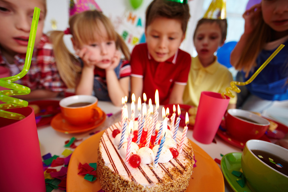 Group Of Adorable Kids Looking At Birthday Cake With Burning Candles