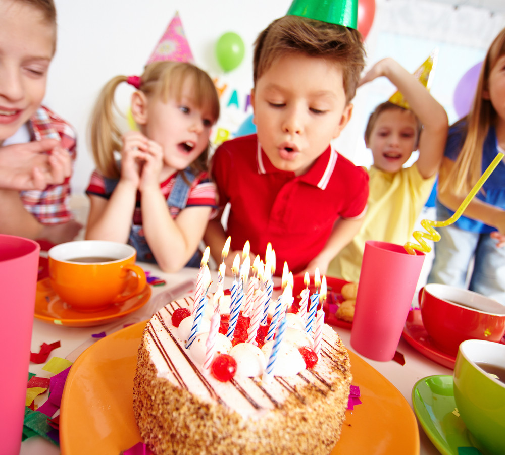 Group Of Adorable Kids Looking At Birthday Cake With Candles