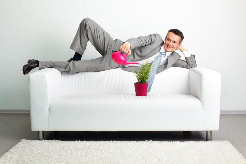 Photo Of Happy Man Watering Plant While Lying On Sofa