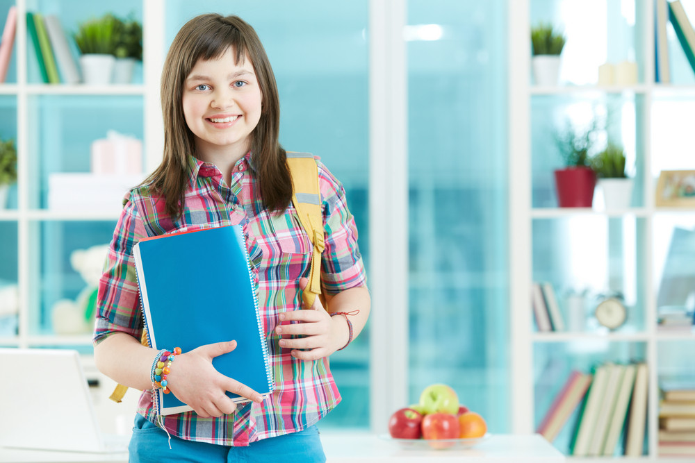 Teenage Girl With Notepad And Backpack Looking At Camera With Smile