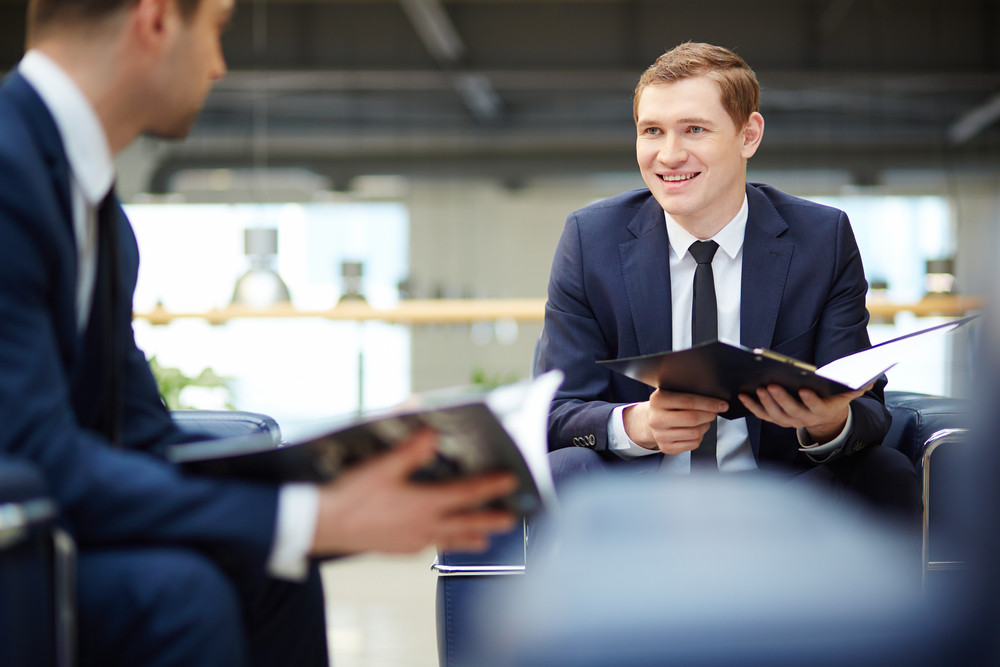 Image Of Two Young Businessmen Communicating At Meeting