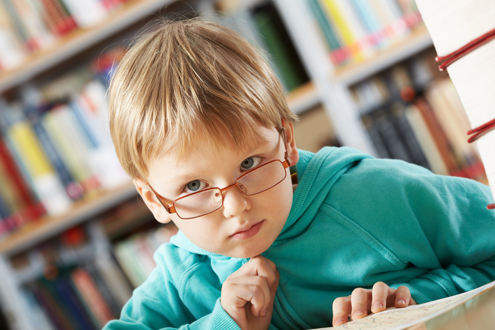 Portrait Of Clever Boy Thinking In Library