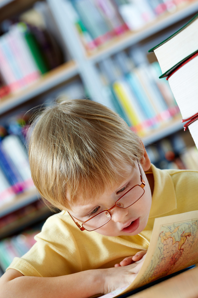 Portrait Of Clever Boy Looking At Map In Library