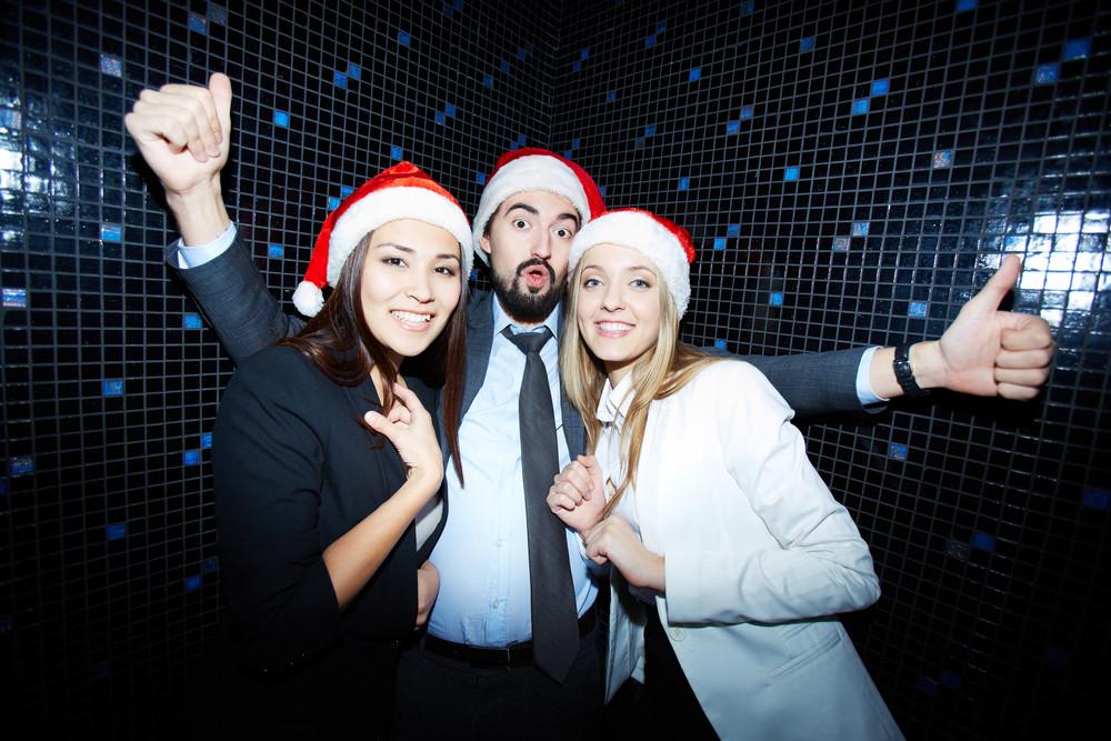 Portrait Of Joyful Colleagues In Santa Caps Having Fun In Nightclub