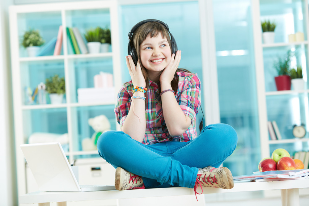 Image Of A Happy Teen Girl Sitting On The Desk And Listening To Music