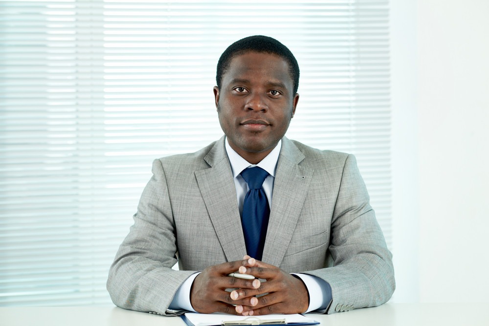 Portrait Of Confident African Businessman Looking At Camera In Office