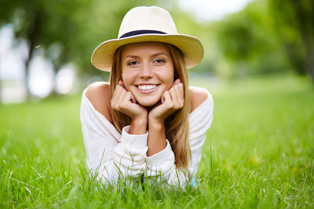 Happy Girl In Hat Lying In Grass And Looking At Camera