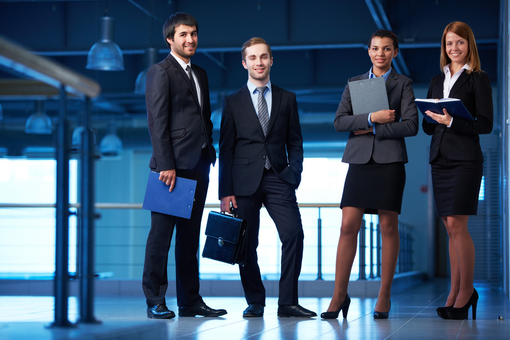 Group Of Friendly Businesspeople In Suits Standing In Line In Office Building